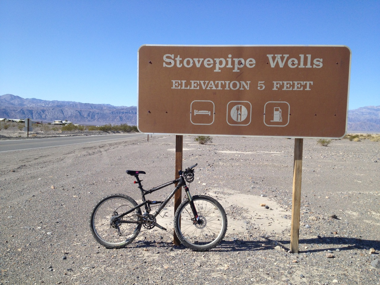 My trusty bicycle resting against the sign for Stovepipe Wells after the ride.