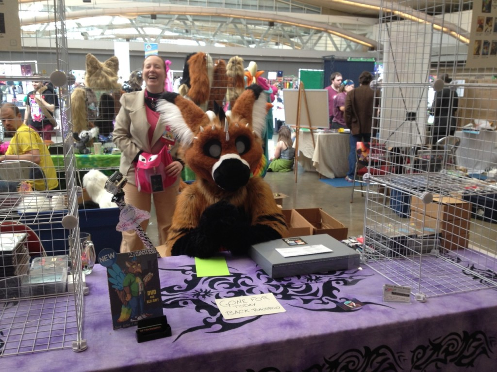 My friend Zylana (in back) and the fursuit performer Telephone, at 2's dealer table.